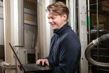 Anställd inom VA håller i en dator och ser lycklig ut.